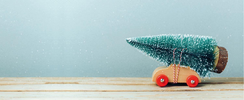 Bild: Holzauto mit Weihnachtsbaum auf dem Dach festgebunden