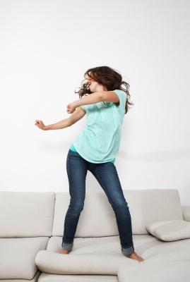 Bild: Frau tanzt auf Couch