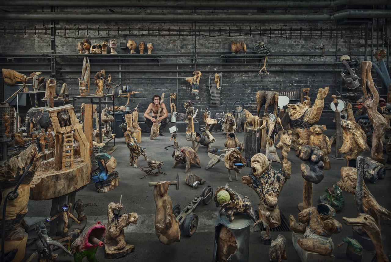 Bild: Künstler Thomas Putze inmitten seiner Skulpturen sitzend