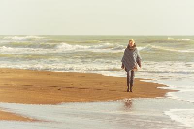 Bild: Frau spaziert am Strand