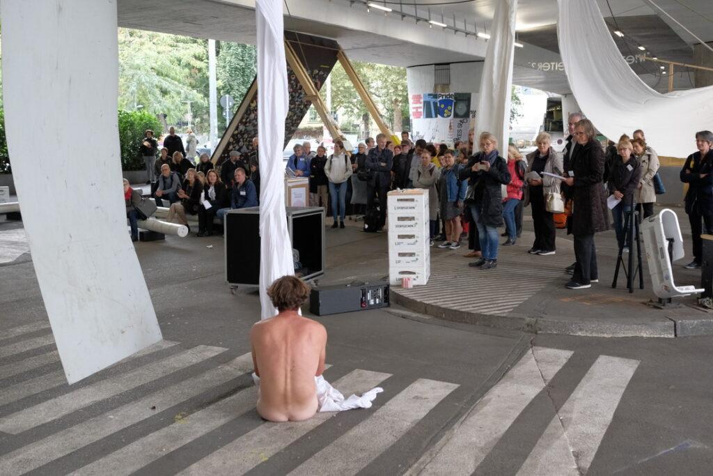 Bild: Künstler sitzt nackt und in Segeltuch gewickelt auf dem Boden
