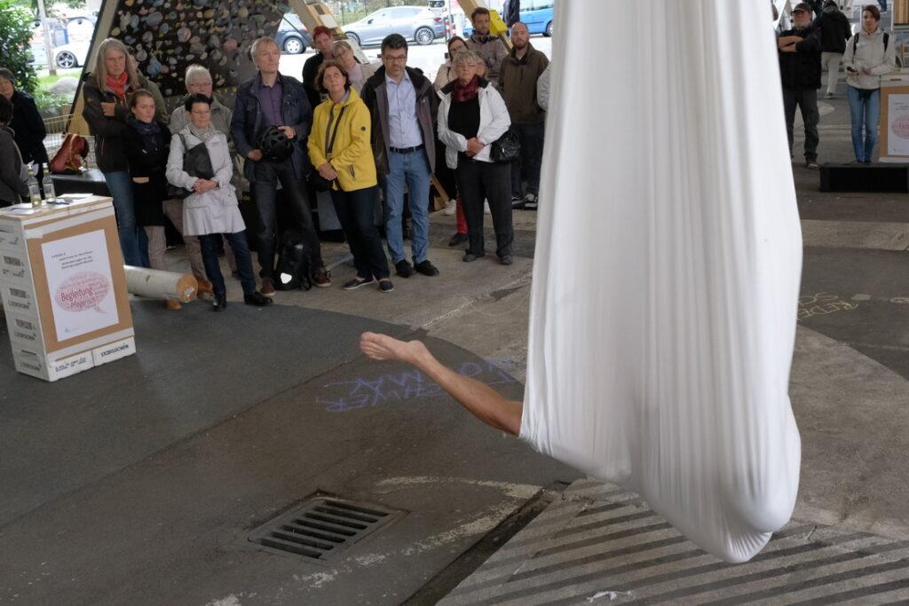 Bild: Künstler in Segeltuch hängt von der Brücke und streckt ein Bein raus