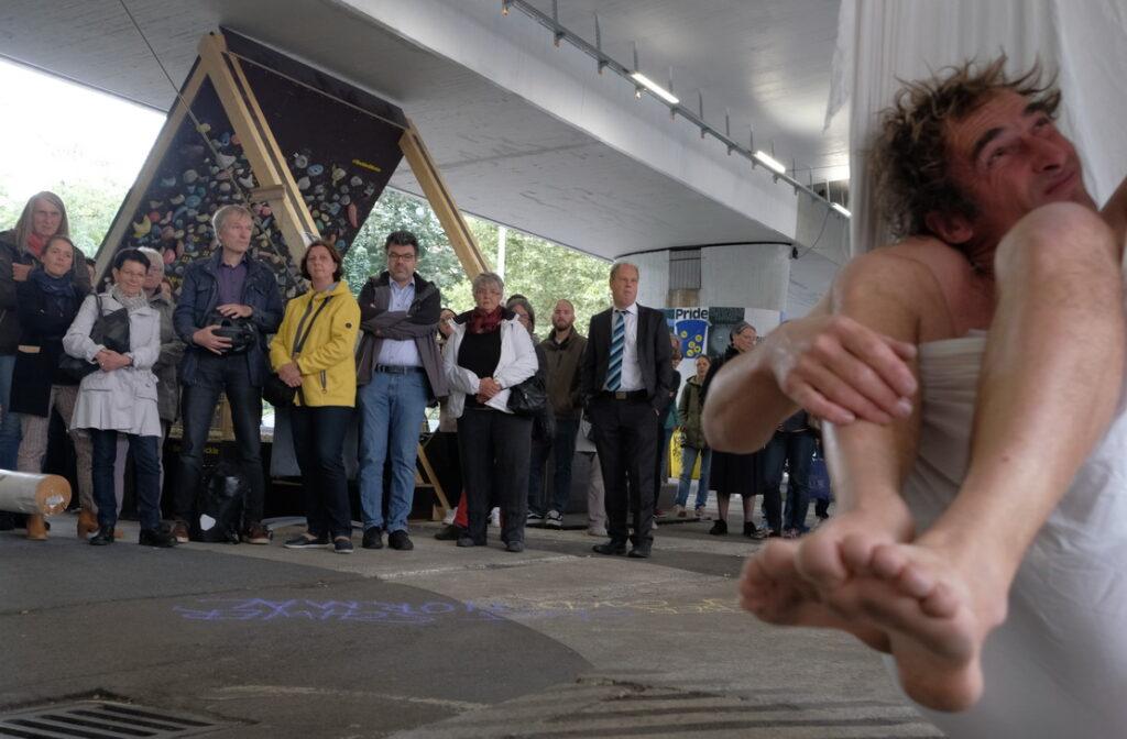 Bild: Künstler in Segeltuch hängt von der Brücke