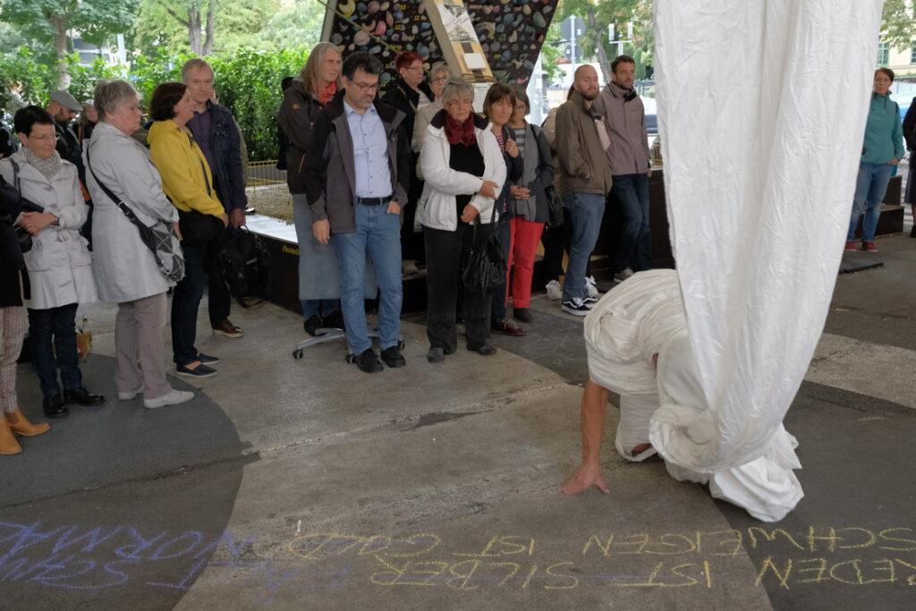 Bild: Künstler kriecht mit umwickeltem Kopf am Boden