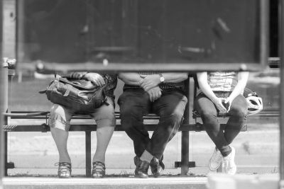 Bild: Menschen sitzen an einer Haltestelle