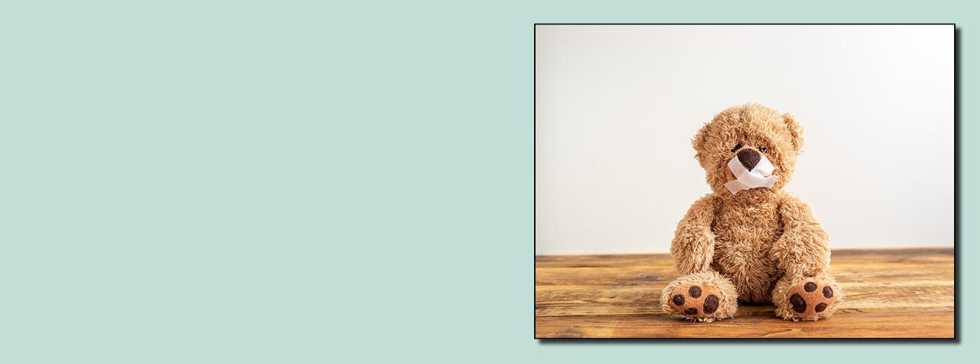 Bild: Banner Teddy sitzt mit zugeklebtem Mund mit Pflaster