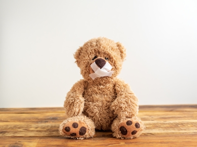 Bild: teddy sitzt mit Pflaster über dem Mund